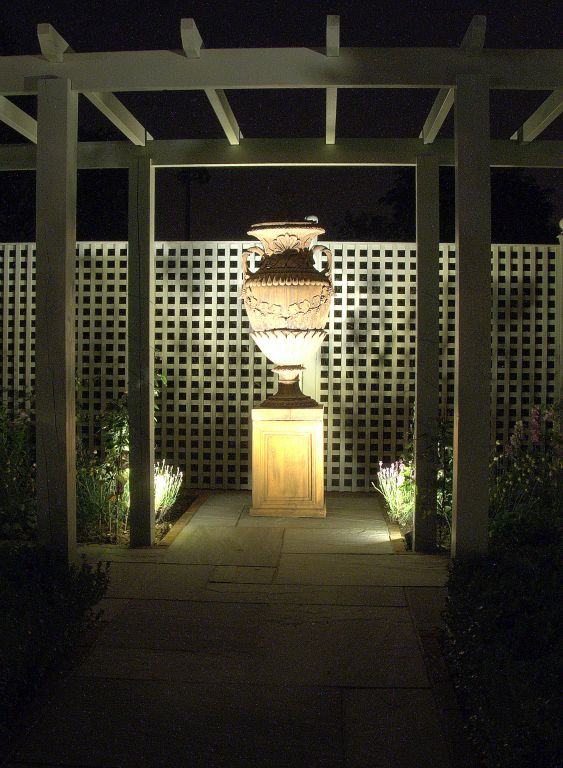 Lighting on urn and trellis in pergola