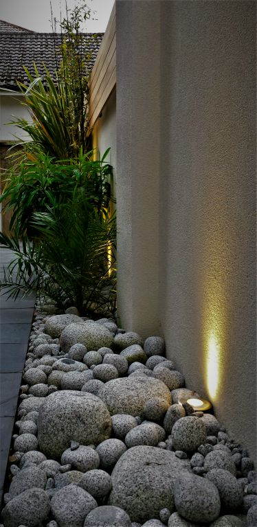 Walled garden lighting with pebbles